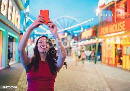 Beautiful girl taking photos at the amusement park