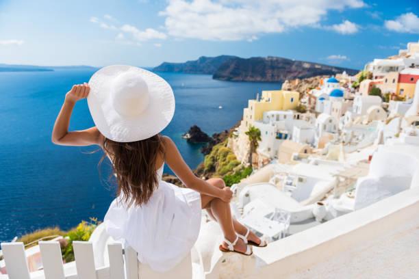 Tourist Enjoying The View Of Oia Village Santorini stock photo