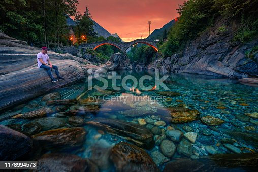 Tourist relaxes at the Verzasca river and enjoys colorful sunset above the double arch stone bridge at Ponte dei Salti in Lavertezzo, Canton Tessin, Switzerland