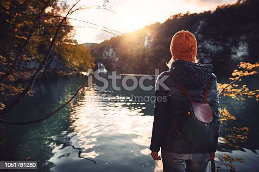 Woman tourist exploring Plitvice Lakes National Park at sunny autumn day. Croatia