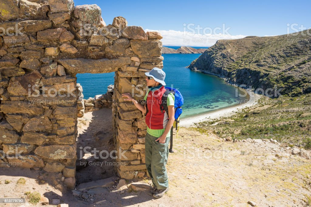 Tourist exploring the ancient mysterious Inca labyrinth-like settlement, called Chinkana, on the Island of the Sun, Titicaca Lake, Bolivia. Travel adventures the Americas. stock photo