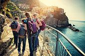 Family walking the azure trail between Corniglia and Manarola in Cinque Terre National Park - a UNESCO World Heritage Site. \nNikon D850