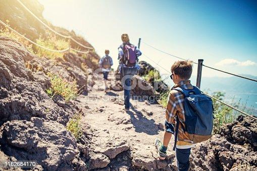 Family hiking on Mount Vesuvius volcano in Campania, Italy. Sunny summer day. Nikon D850