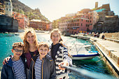 Family sightseeing beautiful Italian town of Vernazza.  One of the five towns in Cinque Terre National Park - a UNESCO World Heritage Site. The family taking selfie using a selfie stick.\nNikon D850