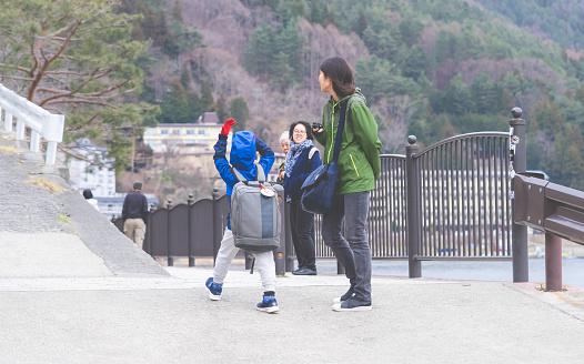 Tourist family is walking on Kawaguchiko lake.