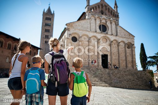 Tourist family sightseeing little Italian town. Mother is showing the church and explaining history to the children. Nikon D810