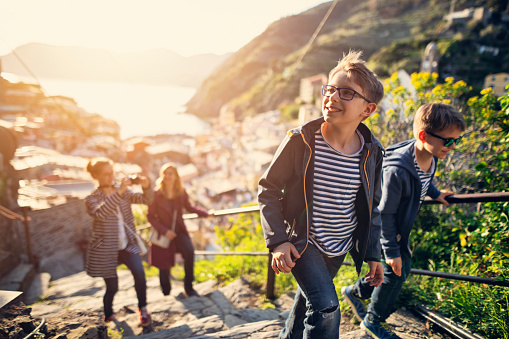 Family sightseeing beautiful Italian town of Vernazza.  One of the five towns in Cinque Terre National Park - a UNESCO World Heritage Site. The family walking on a trail on hills near Vernazza. The panorama of the town is visible in the behind in the glorious sunset light.\nNikon D850