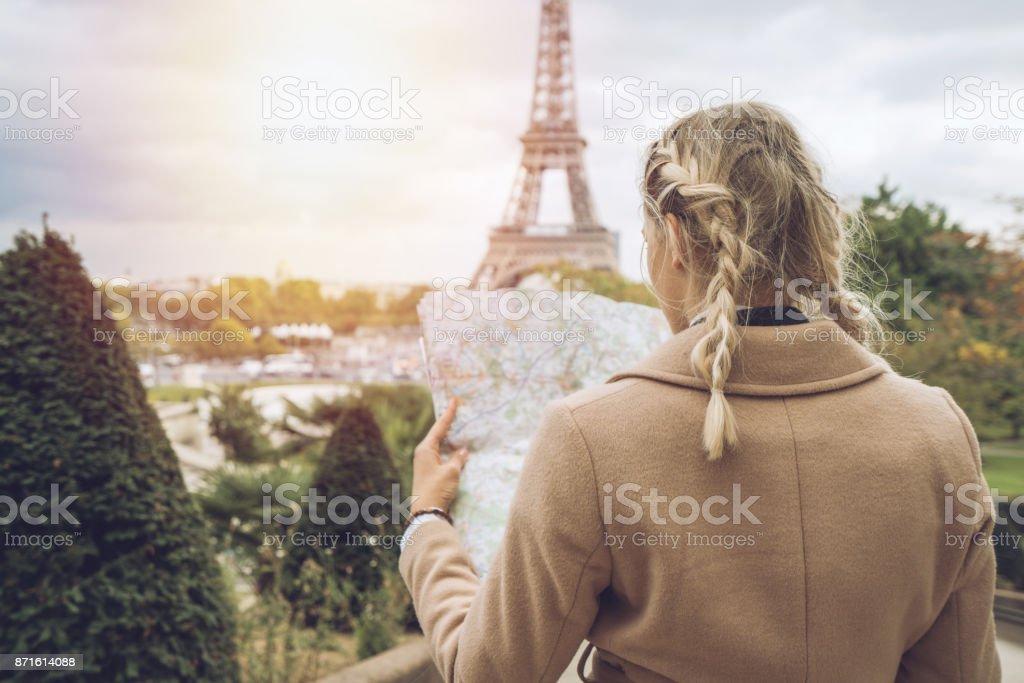 Tourist-Weibchen in Paris am Eiffelturm im Besitz einer Karte – Foto