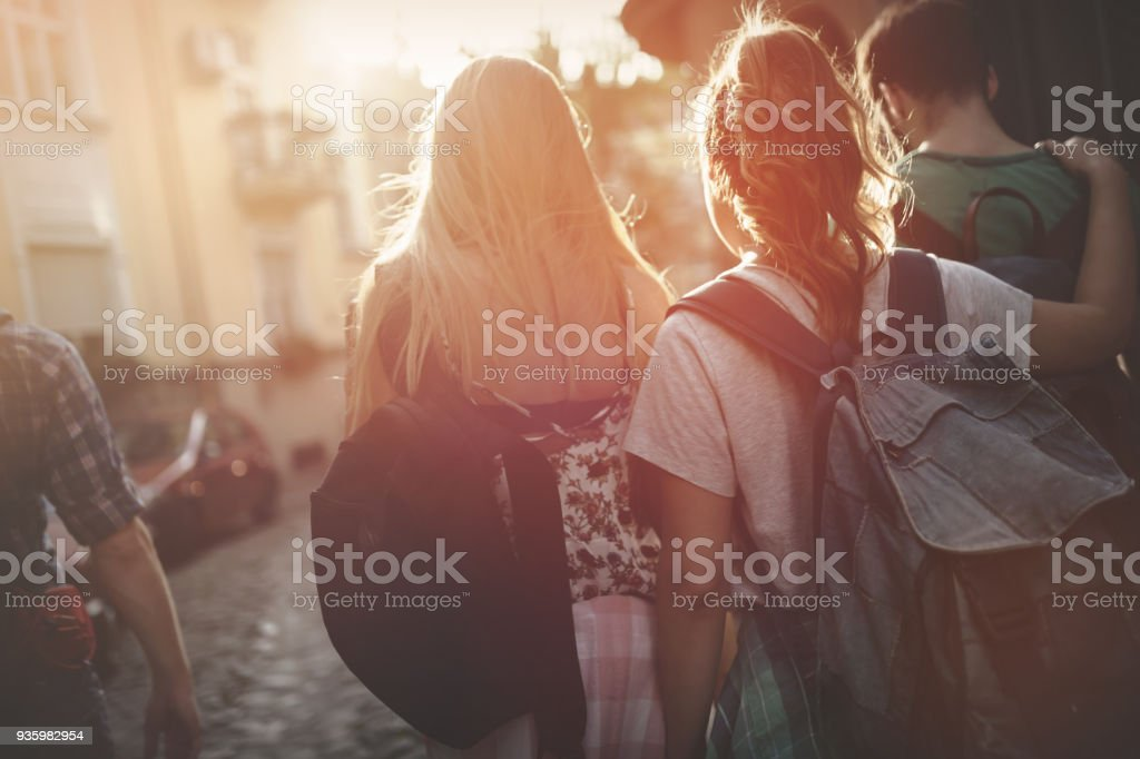 Tourist friends discovering city on foot stock photo