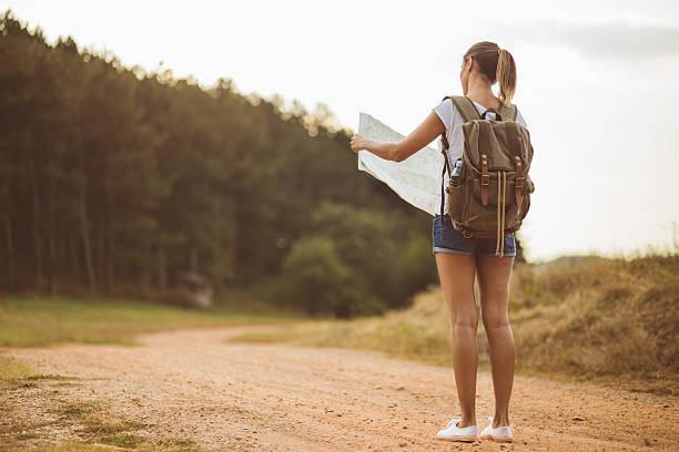 tourist girl checking out locatig map - geführtes lesen stock-fotos und bilder
