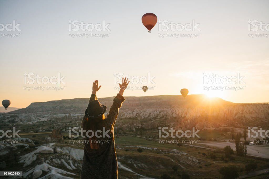 A tourist girl in a hat admires hot air balloons flying in the sky over Cappadocia in Turkey. Impressive sight. stock photo