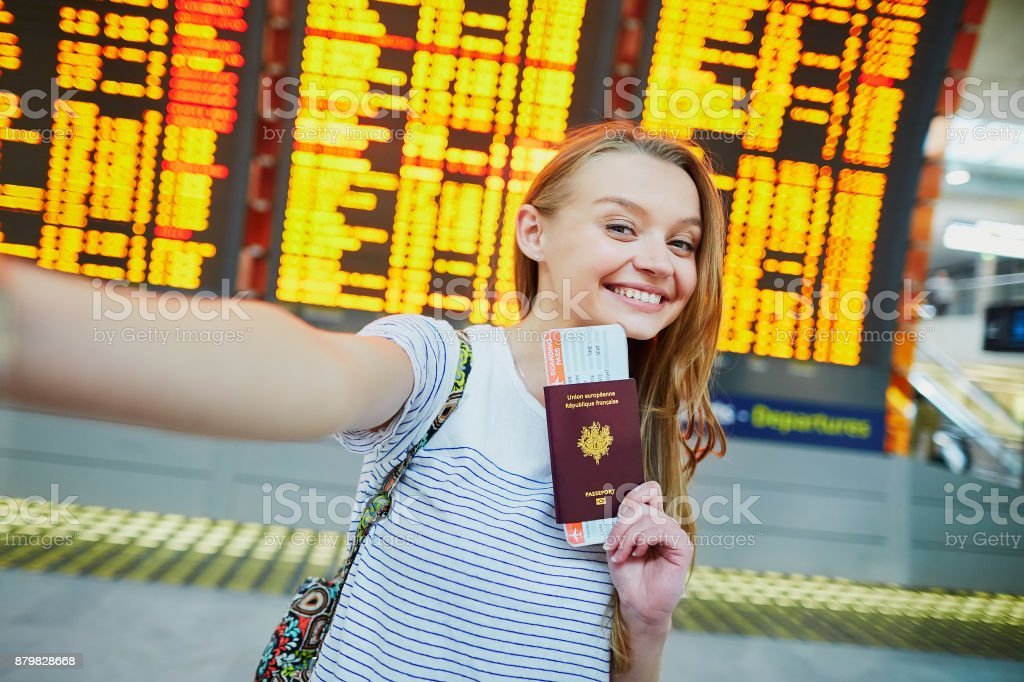 Tourist girl in airport, taking funny selfie with passport stock photo