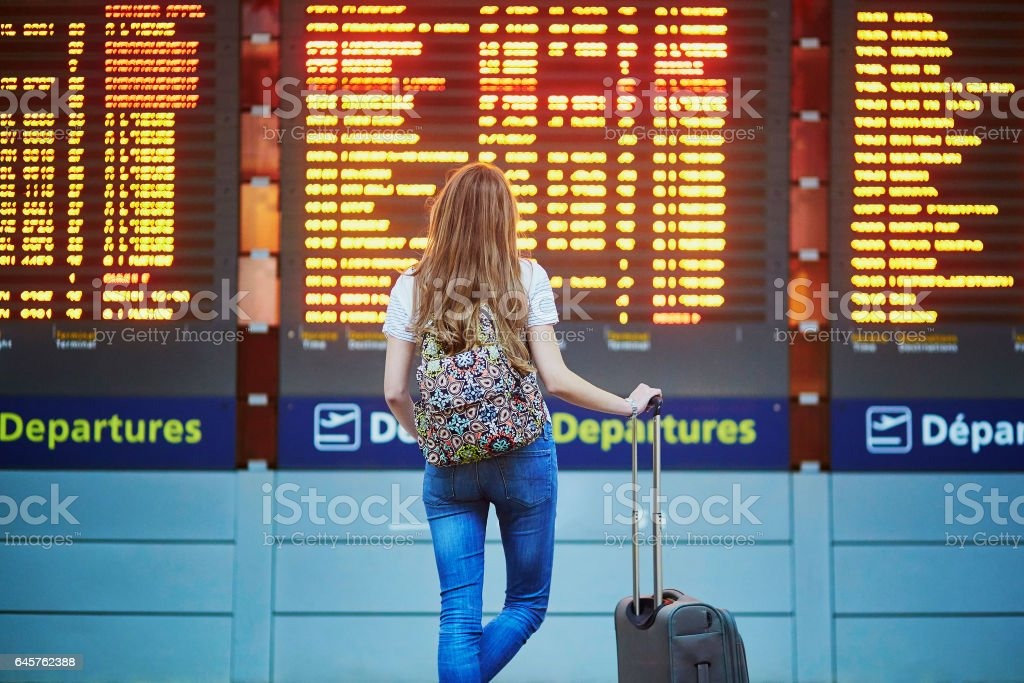 Tourist girl in international airport, near flight information board stock photo