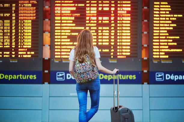 tourist girl in international airport, near flight information board - arrival departure board stock photos and pictures