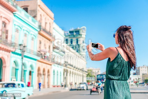 Tourist girl in popular area in Havana, Cuba. Young woman traveler taking foto of famous area