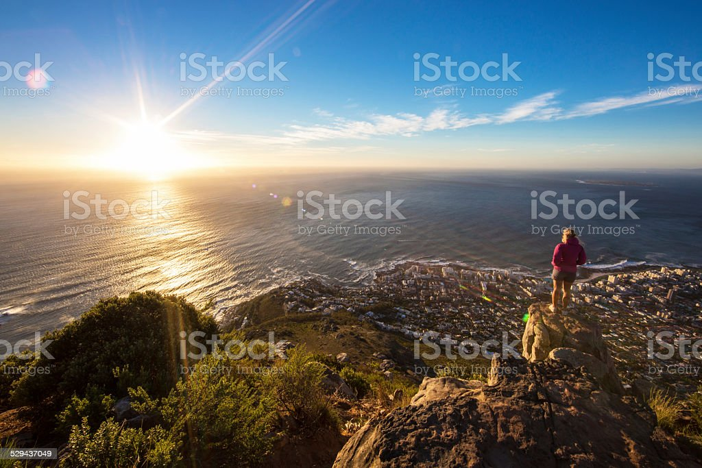 Tourist girl looking into the sunset stock photo