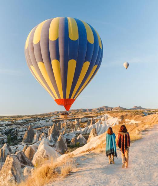 a tourist girl on a mountain top enjoying wonderful view of the sunrise and balloons in cappadocia. happy travel in turkey concept - balão enfeite imagens e fotografias de stock