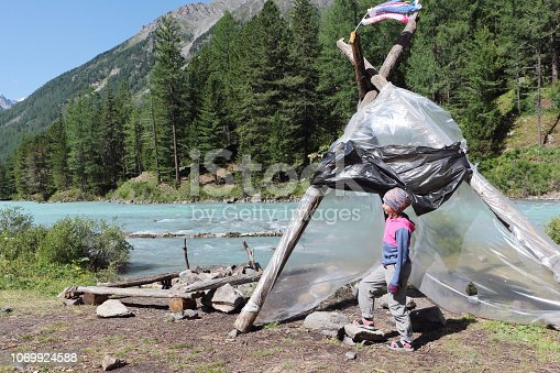 istock Tourist girl standing near  protective awning on the bank of a mountain river,Kucherla River, Altai Mountains, Russia 1069924588