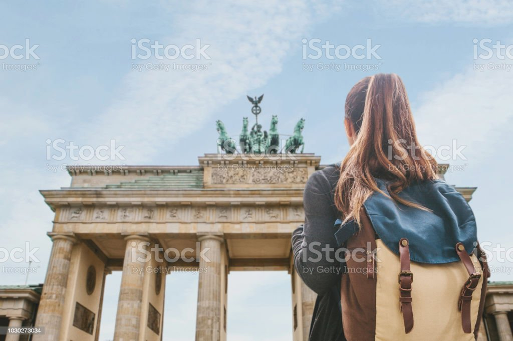 A tourist girl with a backpack looking at the Brandenburg Gate in Berlin royalty-free stock photo