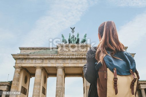 istock A tourist girl with a backpack looking at the Brandenburg Gate in Berlin 1030273034