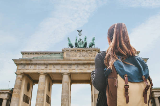 A tourist girl with a backpack looking at the Brandenburg Gate in Berlin stock photo