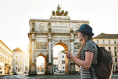 A tourist girl with a backpack looks sights in Munich in Germany. Passes by the triumphal arch.