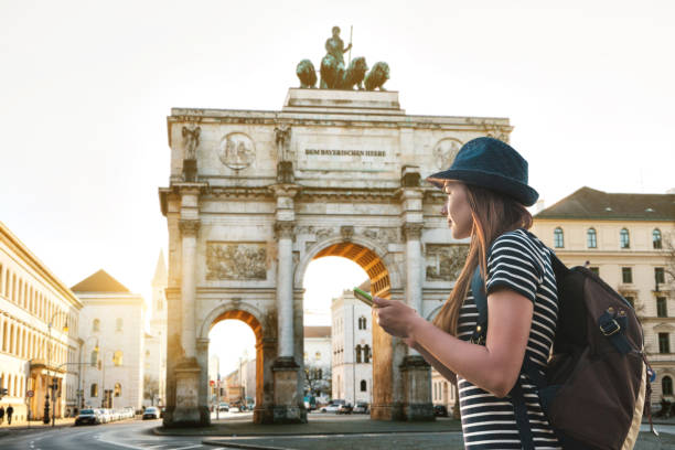 A tourist girl with a backpack looks sights in Munich in Germany A tourist girl with a backpack looks sights in Munich in Germany. Passes by the triumphal arch. germany stock pictures, royalty-free photos & images