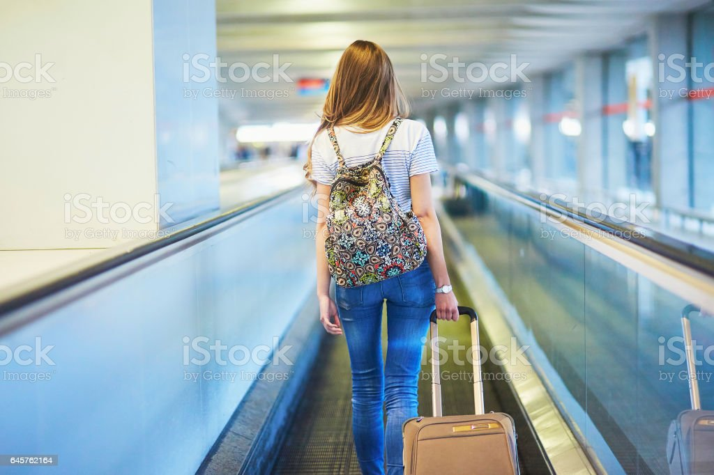 Tourist girl with backpack and luggage in international airport stock photo