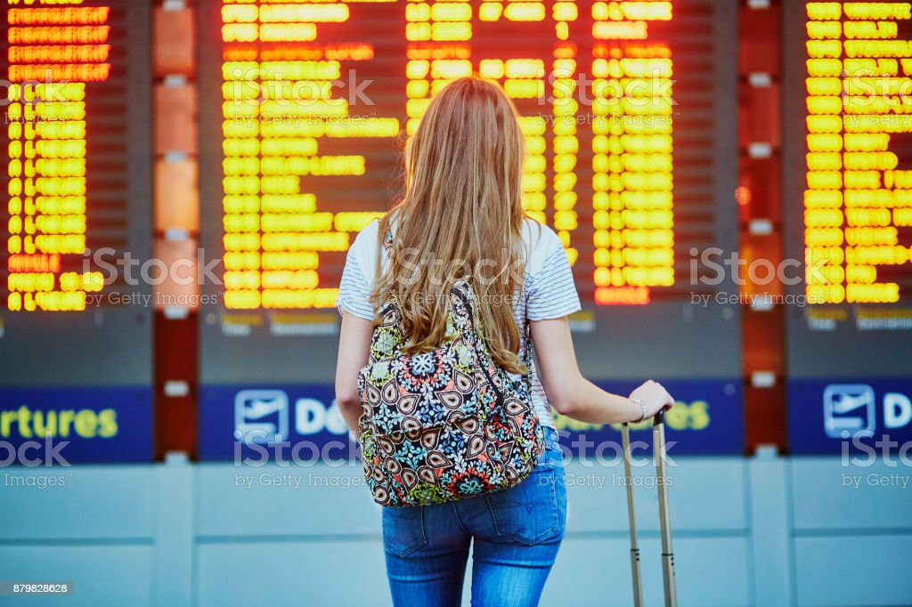 Tourist girl with backpack in international airport stock photo