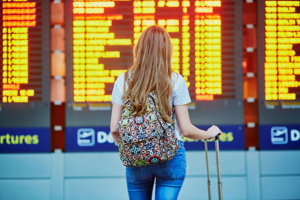 tourist girl with backpack in international airport - aereo di linea foto e immagini stock