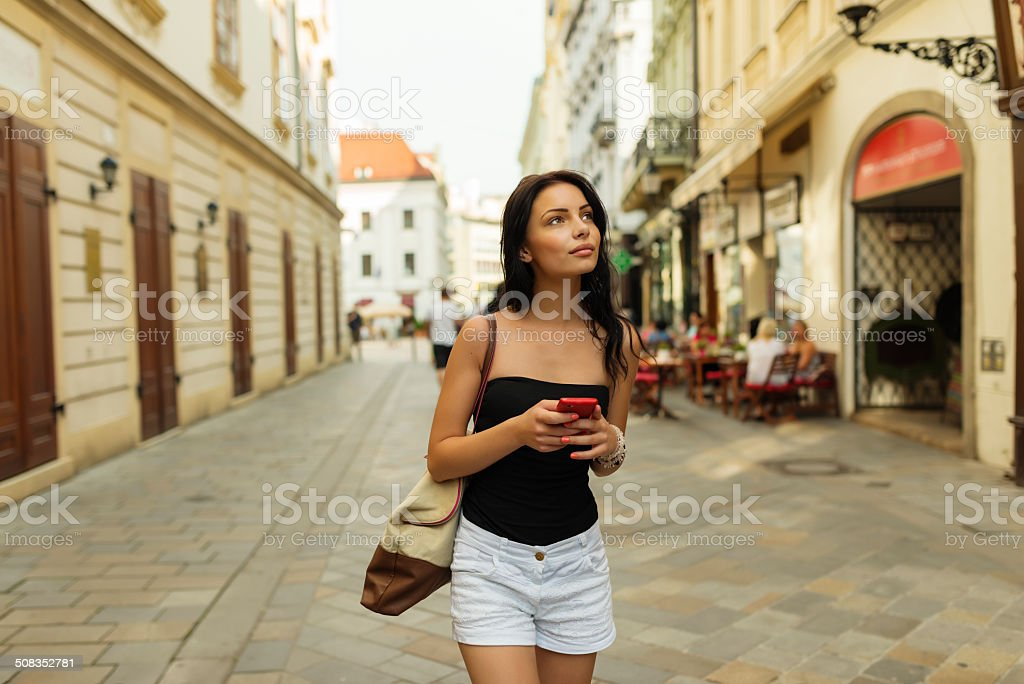Tourist girl with map in smartphone on the street stock photo