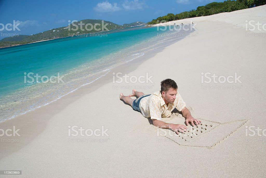 Tourist Guy Lies on Beach with Sand Laptop royalty-free stock photo