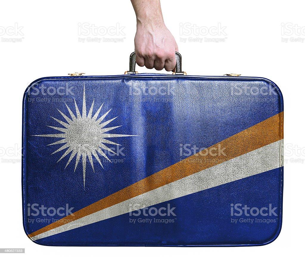 Tourist hand holding vintage travel bag flag of Marshall Islands stock photo
