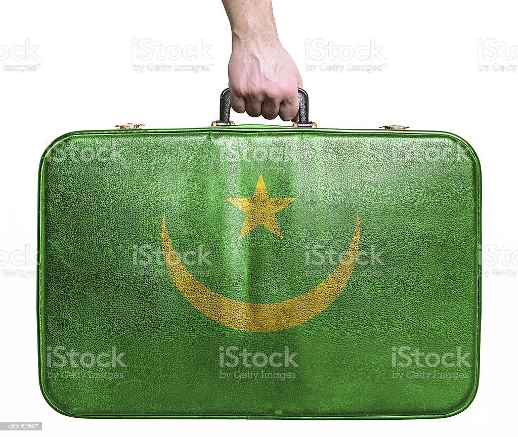 Tourist hand holding vintage travel bag with flag of Mauritania stock photo