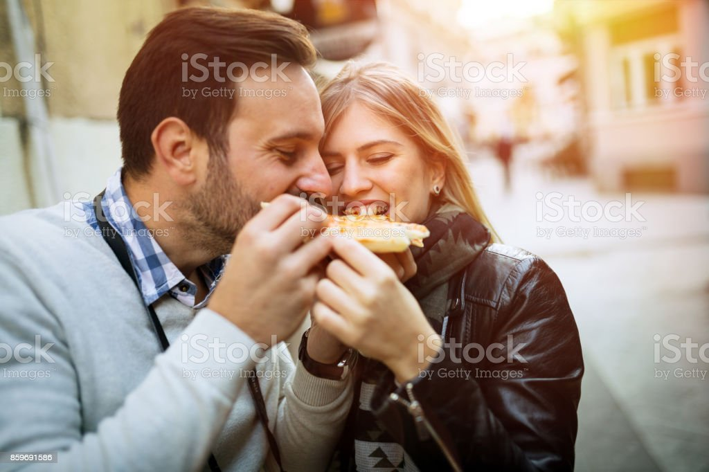 Tourist happy couple sharing pizza stock photo