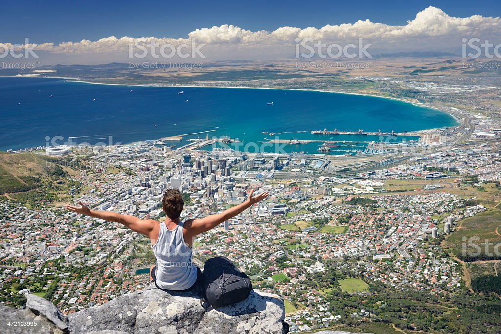 Tourist Hiker on Table Mountain overlooking Cape Town, South Africa Tourist Hiker on Table Mountain overlooking Cape Town, South Africa. You can see the Cape Town Stadium on the left beside the Victoria and Alfred Waterfront. Down Town Cape Town, the Harbor all the way over Bloubergstrand to Atlantis.  Adult Stock Photo