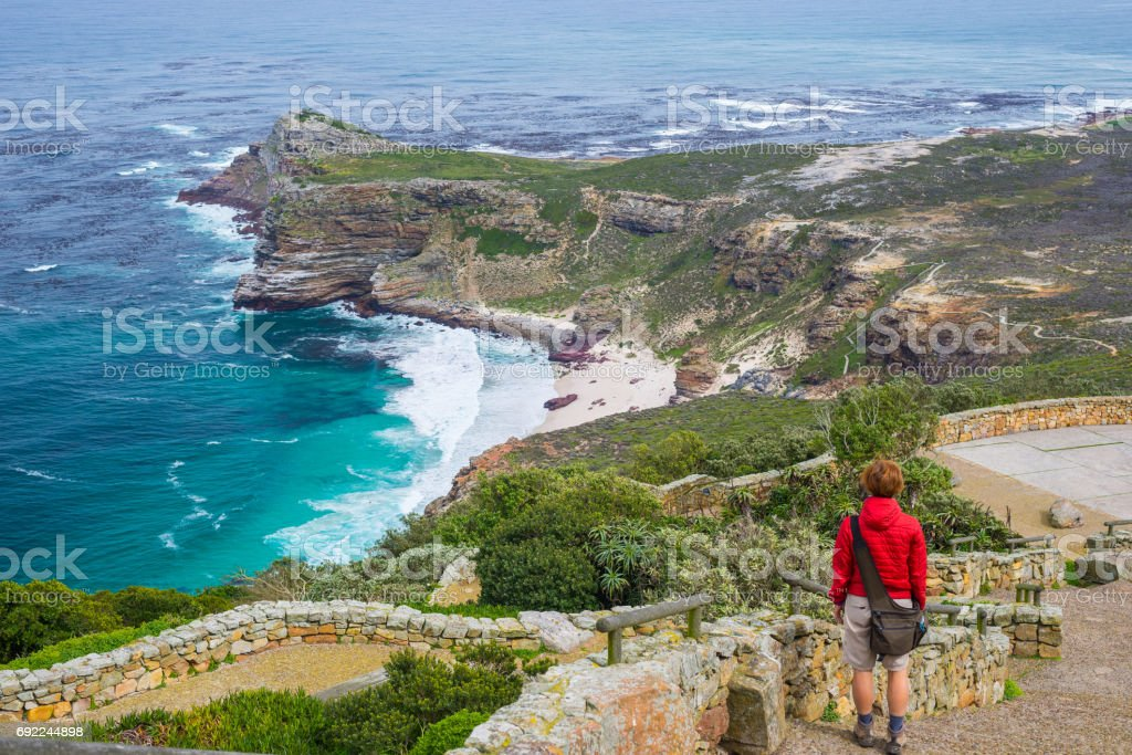 Tourist hiking at Cape Point, looking at view of Cape of Good Hope and Dias Beach, scenic travel destination in South Africa. Table Mountain National Park, Cape Peninsula. stock photo