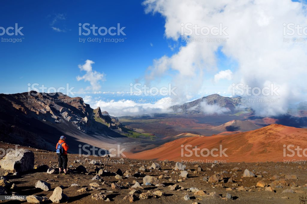 Tourist hiking in Haleakala volcano crater on the Sliding Sands trail. Beautiful view of the crater floor and the cinder cones below. Maui, Hawaii stock photo