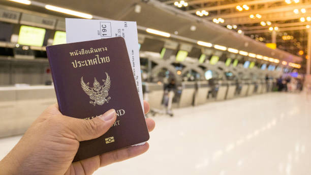 Tourist hold passport and boarding pass at the counter for check-in. Tourist hold passport and boarding pass at the counter for check-in and travel in the airport. Passport and boarding pass for travel concept. pasport malaysia stock pictures, royalty-free photos & images