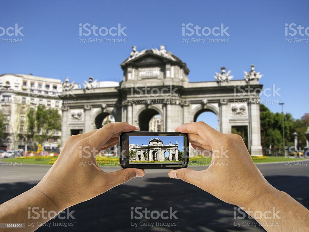 tourist holds up camera phone at Puerta de Alcala royalty-free stock photo
