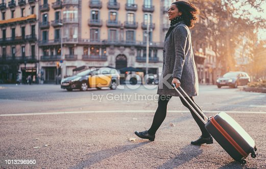 Young woman with suitcase enjoying Barcelona