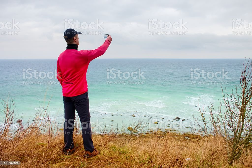 Tourist in baseball cap and pink windcheater takes ocean photo stock photo