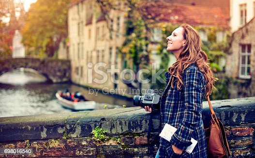 Young woman with a camera enjoying travel to Bruges, Belgium