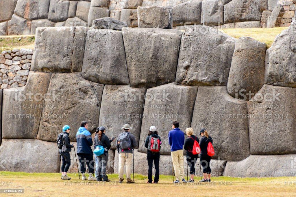 Tourist in front of huge stone wall at Saqsaywaman, Peru stock photo