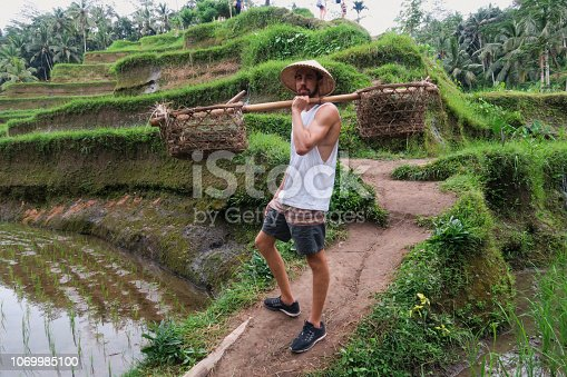 A shot of a Caucasian tourist wearing traditional Asian headwear and holding baskets on a carrying shoulder pole.