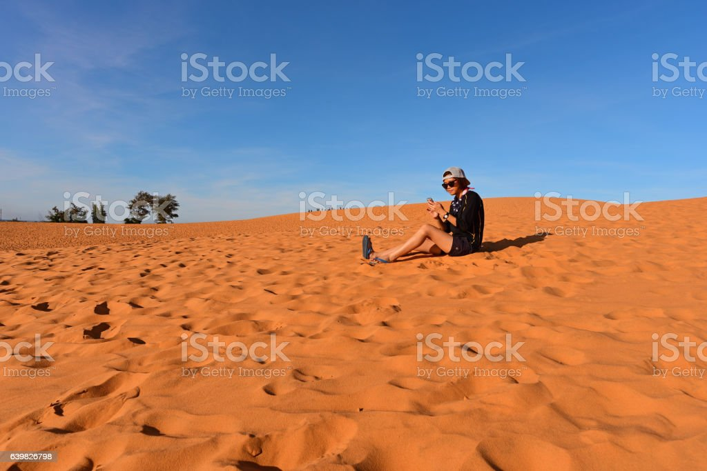 Tourist in red sand dunes stock photo