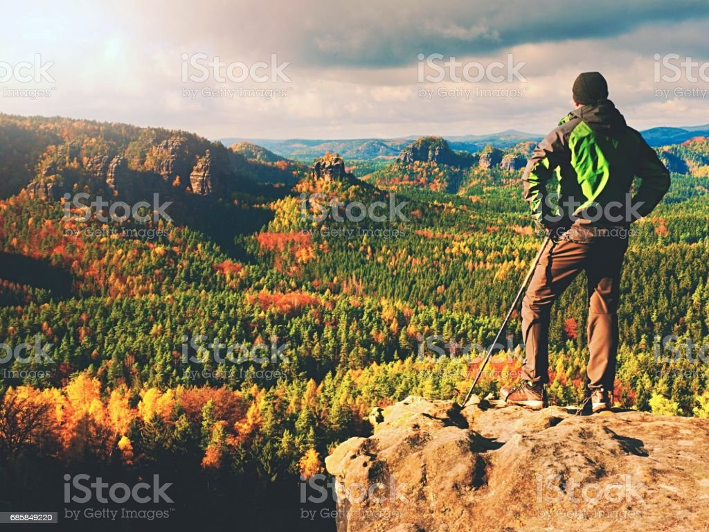 Tourist in sporty  green windcheater with poles in hands on view point watching into landscape. stock photo