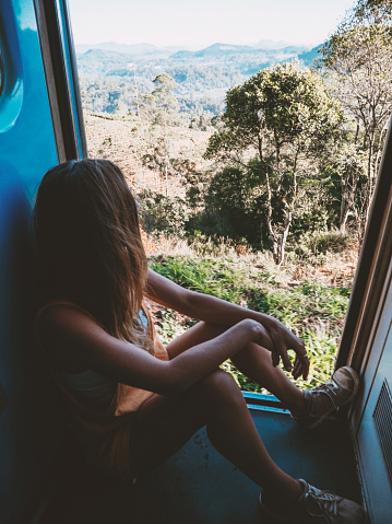 Woman sitting by the door of a moving train contemplating the tea plantations