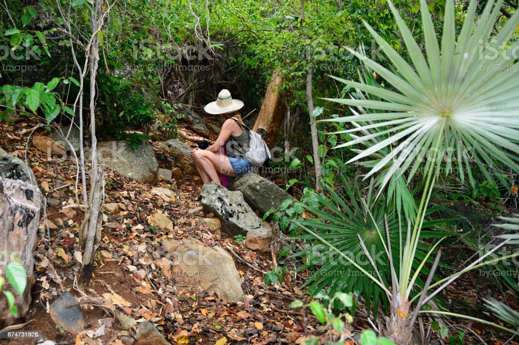 Tourist in the jungle is resting on the stone stock photo