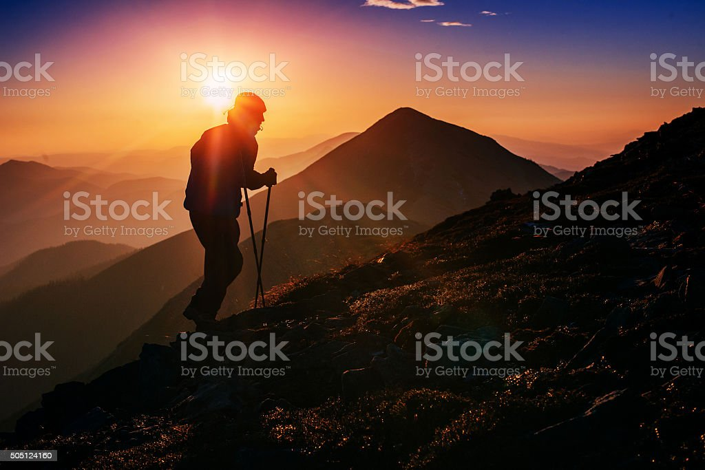 tourist in the mountains at sunset stock photo